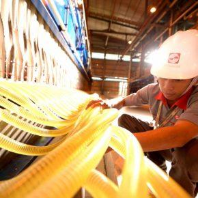 Refinery worker in helmet touching tubes